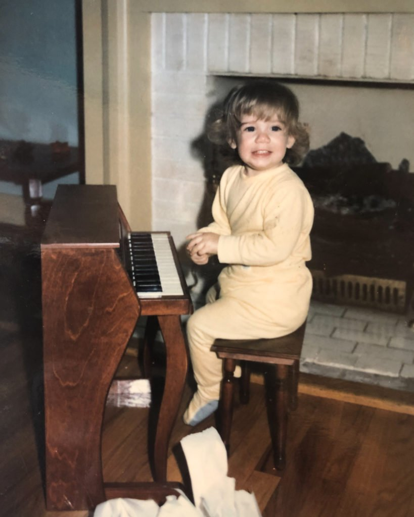 little girl sitting at piano