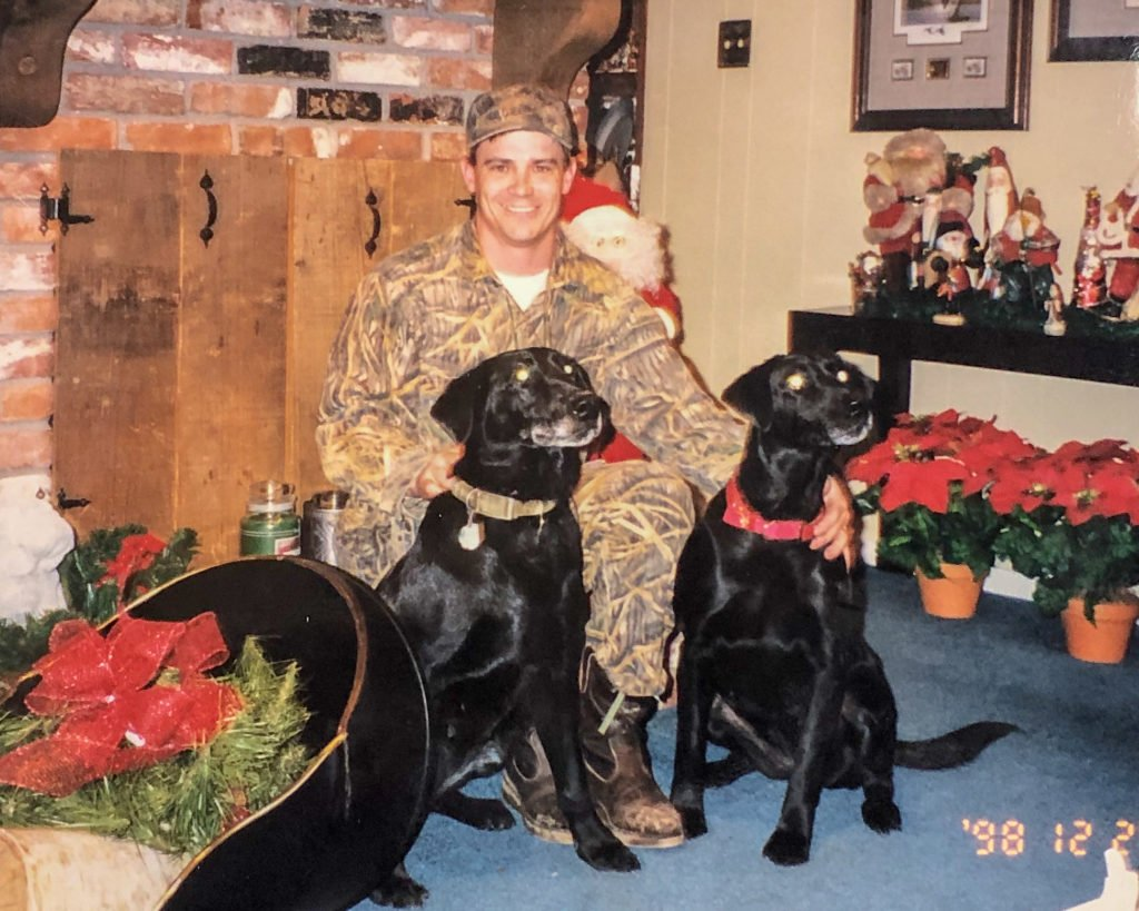 Young man at Christmas sitting with his hunting dogs