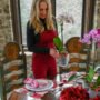 woman standing by table decorated for Valentine's Day holding an orchid