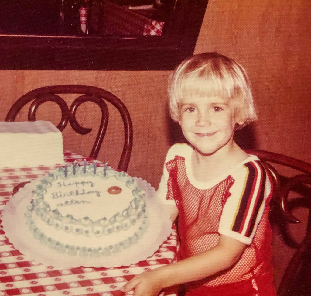 little boy wearing a red shirt and sitting next to his birthday cake