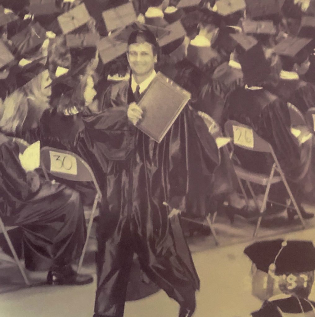 young man wearing cap and gown walking while holding his diploma