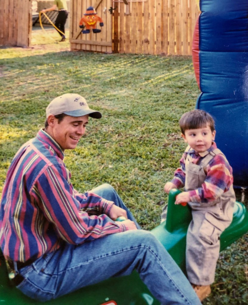 young man and nephew in overalls sitting on green seesaw
