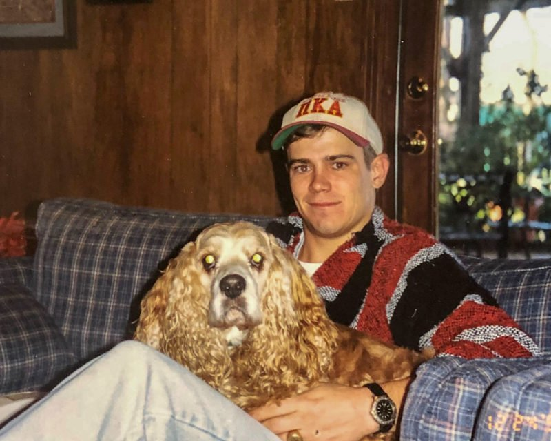young man sitting on couch holding a cocker spaniel