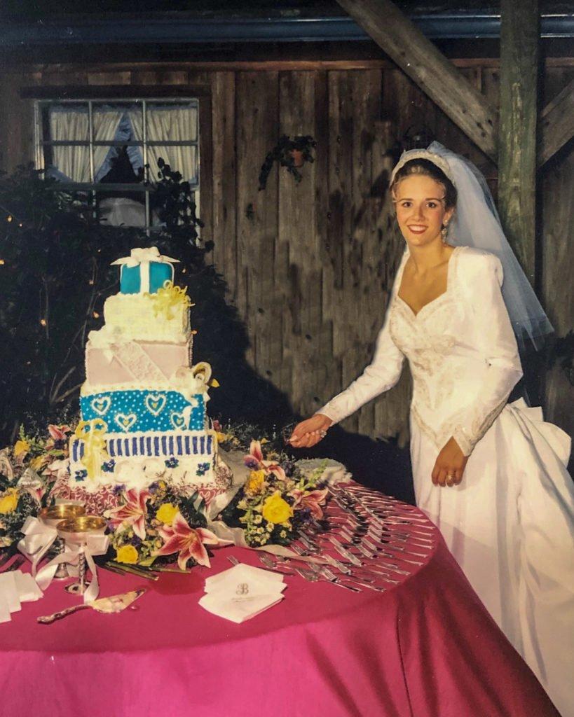 Jennifer Holmes in wedding dress cutting a wedding cake