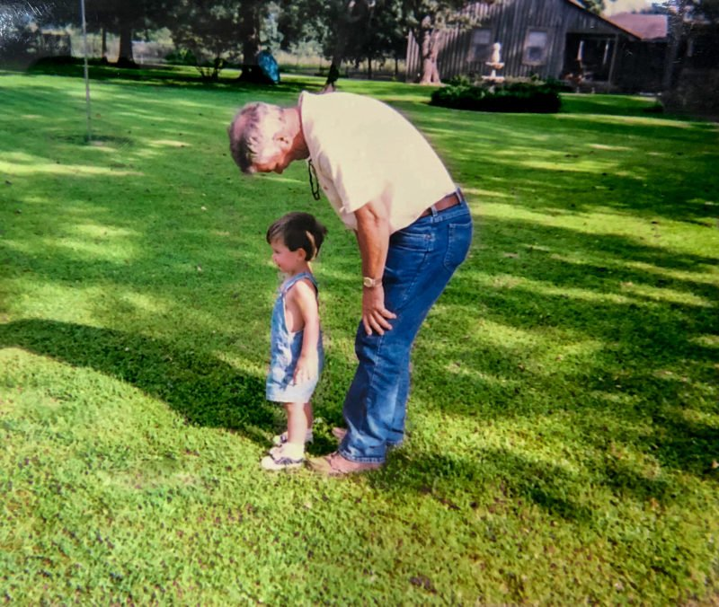 Grandfather and grandson standing in green grass