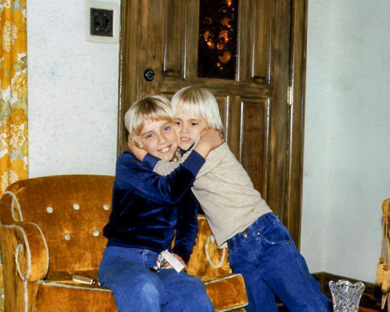 young boy hugging his sister who is sitting down