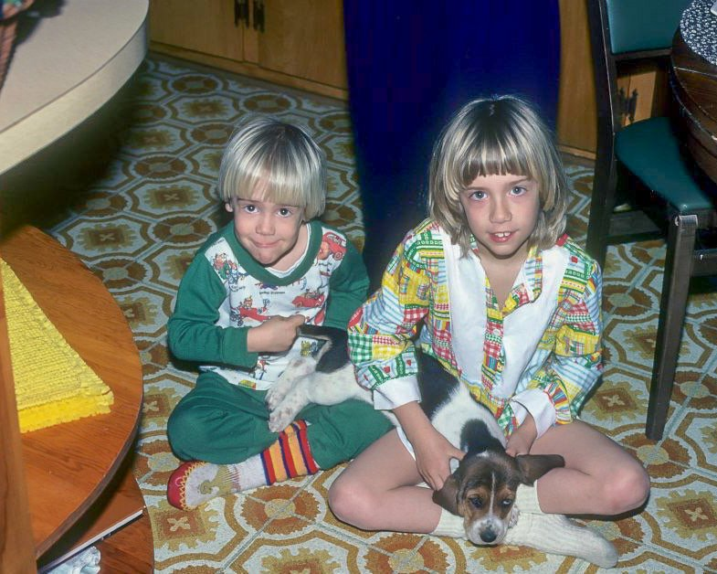 young boy and girl sitting on floor holding a basset hound puppy