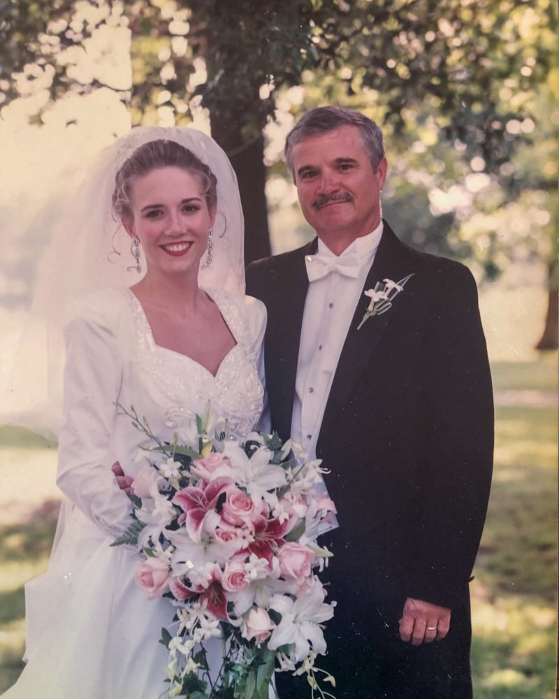 woman in wedding dress holding bouquet standing next to her father