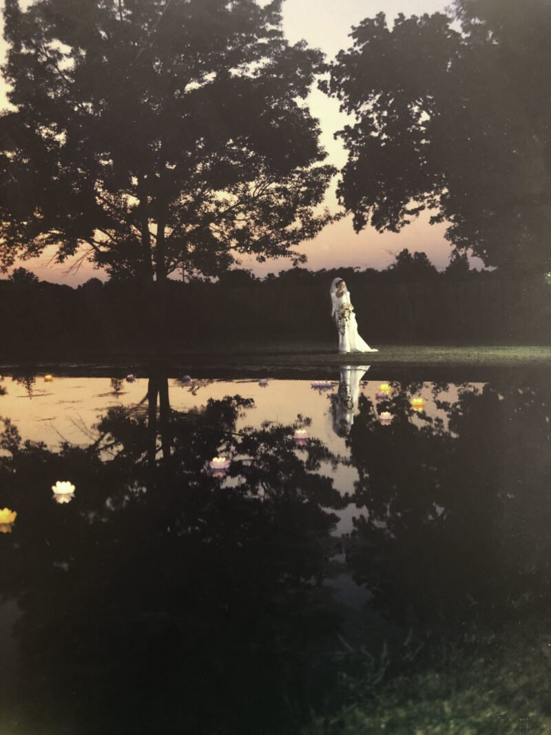 girl in wedding dress next to pond at dusk