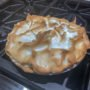 chocolate meringue pie sitting on stove in a kitchen