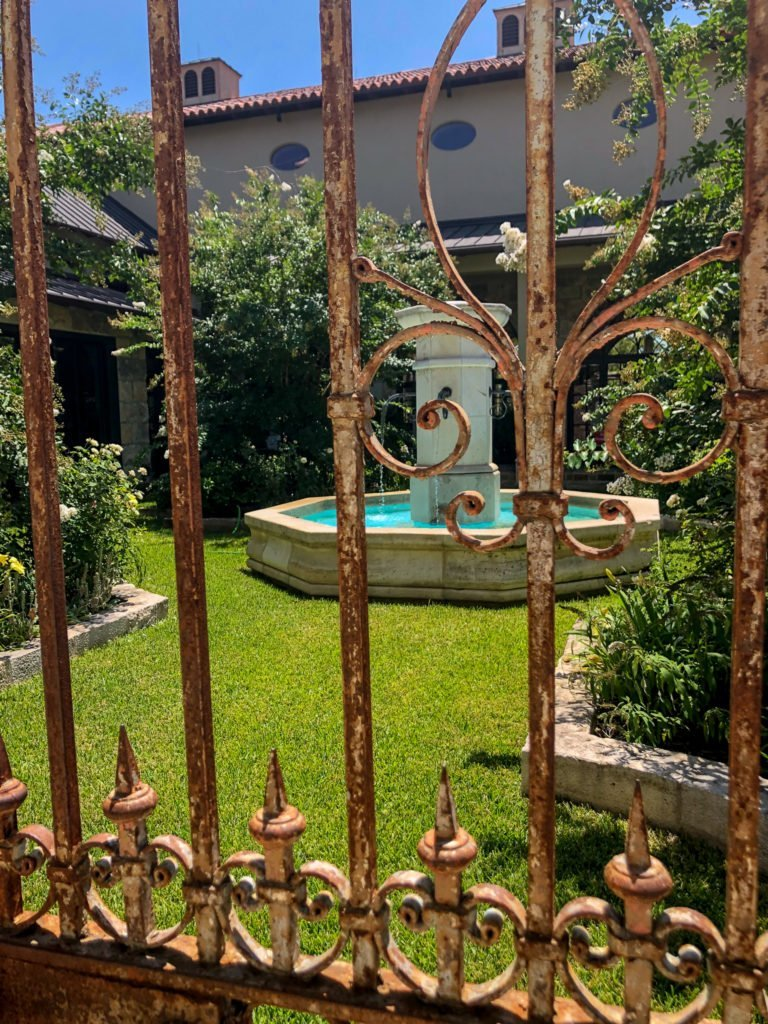 View of courtyard through wrought iron gate - J Dub By Design