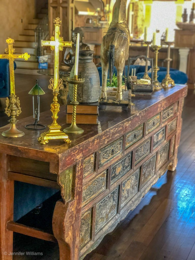 large sofa table in living room with brass crosses and decor