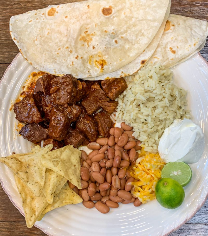 mexican beef flour tortillas beans rice cheese and sour cream on white plate - J Dub By Design
