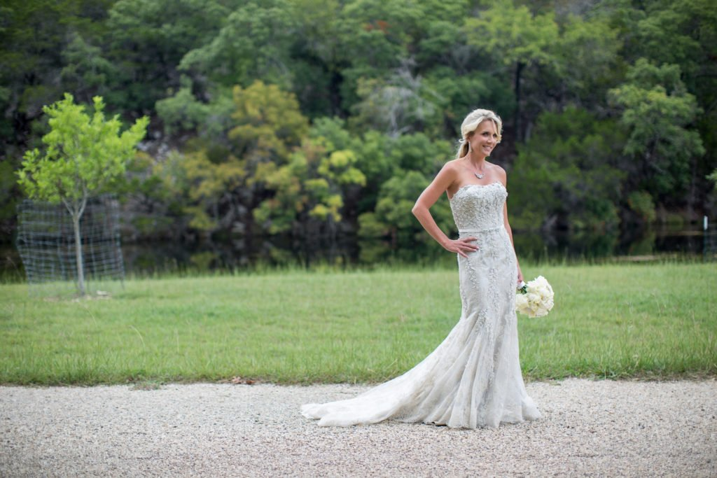 Jennifer Williams standing in wedding dress in front of water - J Dub By Design