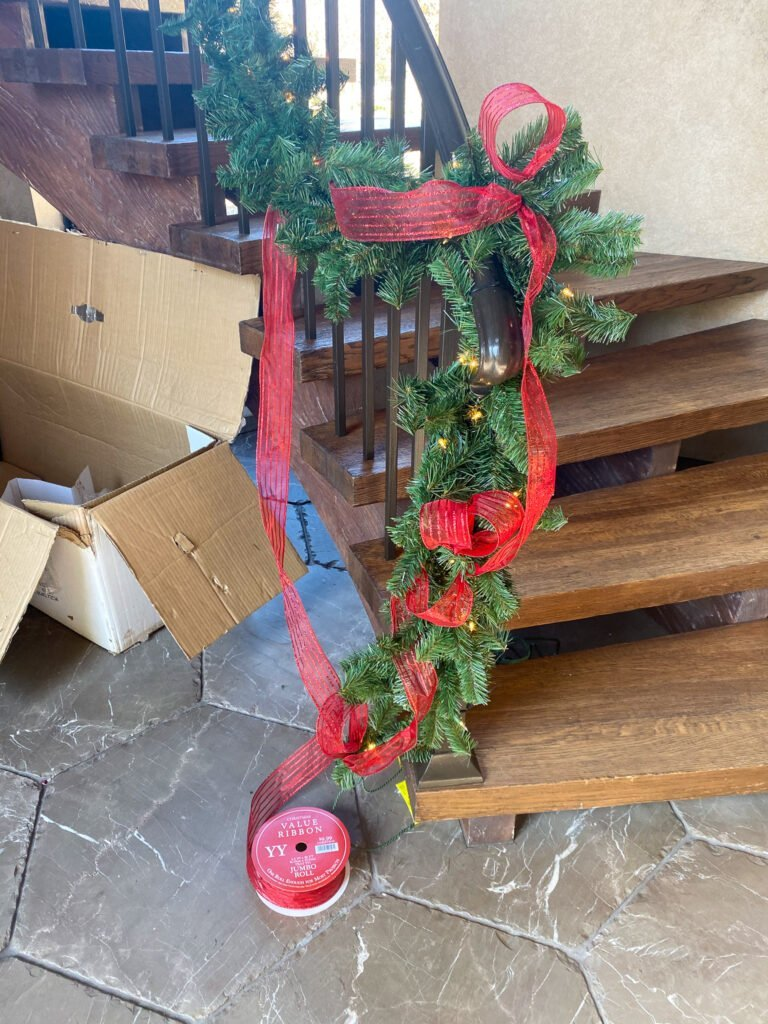 Adding ribbon to garland in stairwell - J Dub By Design