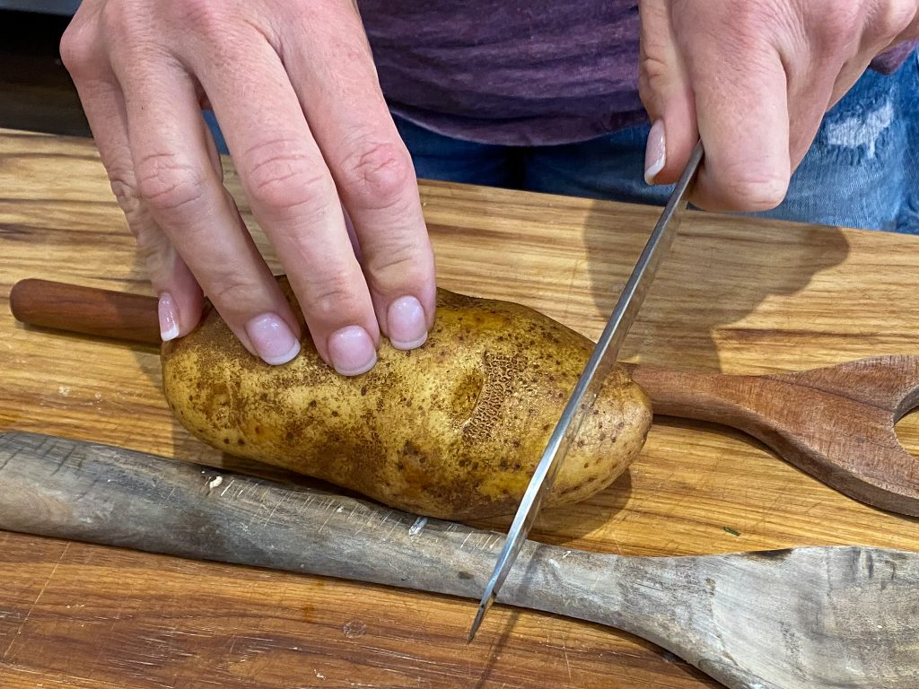 using wooden spoon handles to slice a potato - J Dub By Design