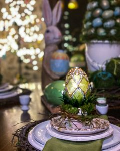 Easter tablescape with large egg sitting in mossy terra cotta pot - J Dub By Design™