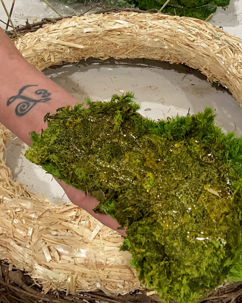 hot gluing large piece of green reindeer moss to straw wreath form - J Dub By Design™