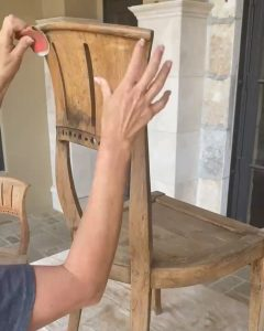 sanding the back of the wooden chairs with 80 grit sandpaper in preparation for stain - J Dub By Design™