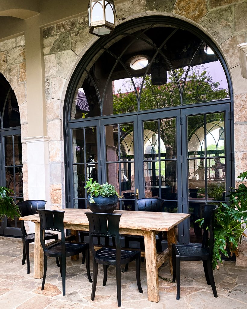 Black and natural wood dining table and chairs on outdoor patio in front of arched glass door - J Dub By Design™