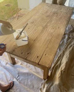 pouring bleach into a plastic container to apply to table - J Dub By Design™