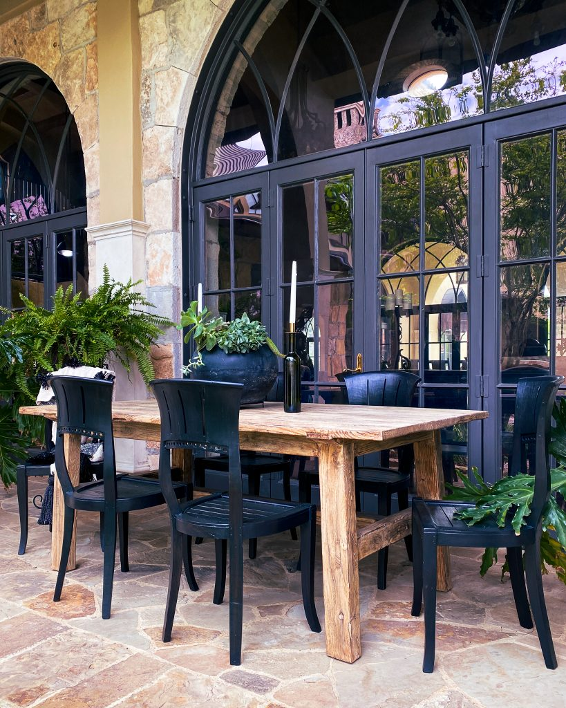 An aged wooden dining room table and black chairs surrounded by ferns and philodendron - J Dub By Design™