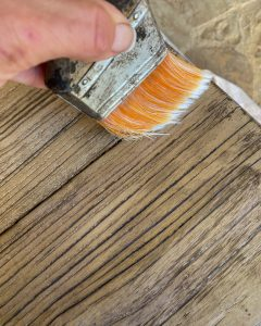 using a synthetic paint brush to feather topcoat to distressed table - J Dub By Design