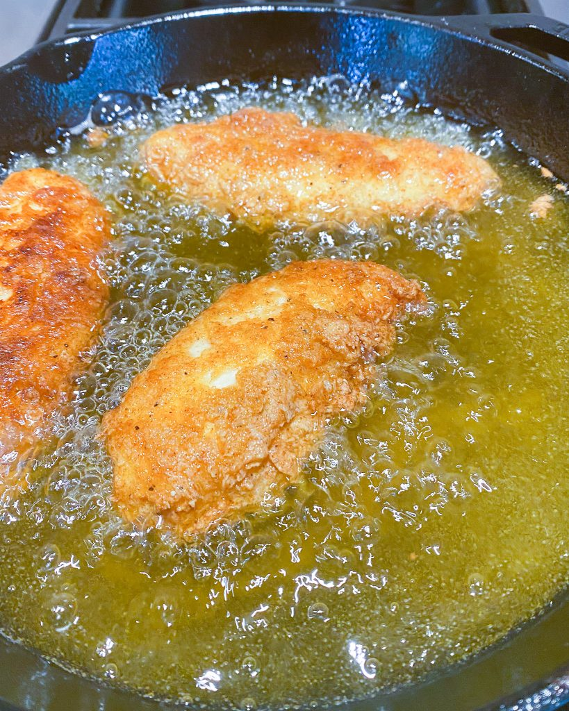 frying chicken tenders in olive oil in cast iron skillet - J Dub By Design™