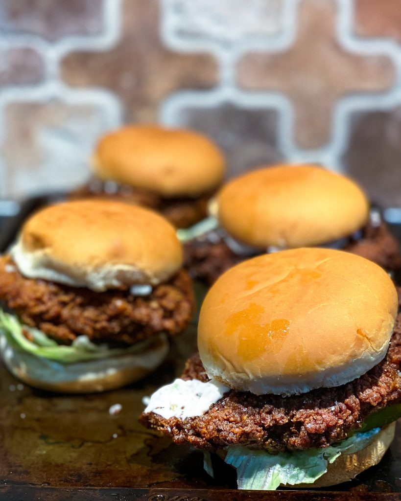 four fried chicken sandwiches sitting on tray in front of tile backsplash - J Dub By Design™