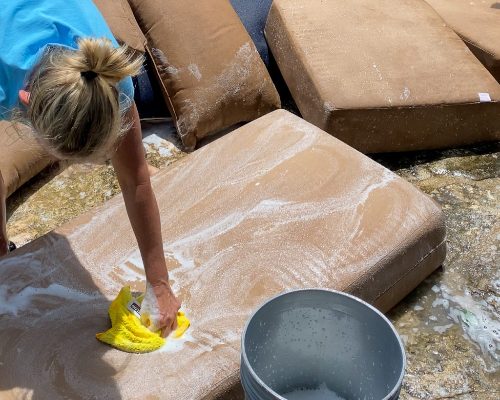 Jennifer Williams cleaning outdoor patio cushions - J Dub By Design™