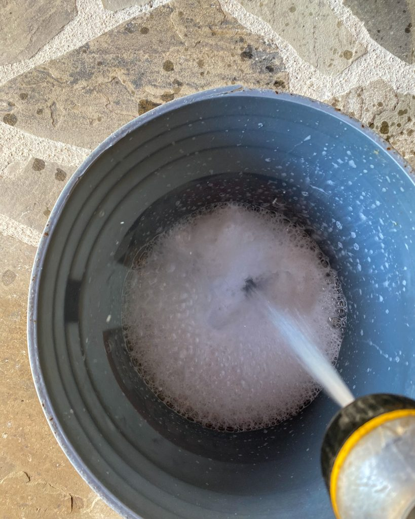 adding water to detergent in 5 gallon bucket to clean patio cushions - J Dub By Design™