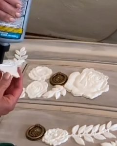 putting glue on the back of resin appliqués to apply to nightstand - J Dub By Design™