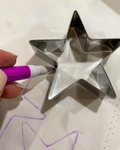 tracing star shapes with invisible marker onto white fabric - J Dub By Design™