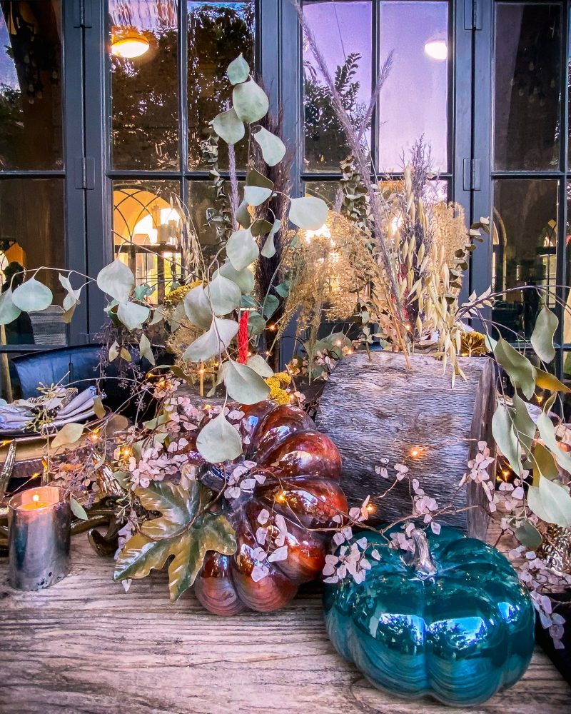 side view of the Fall table-scape using wood remnants, pumpkins, dried florals, and twinkle lights - J Dub By Design™